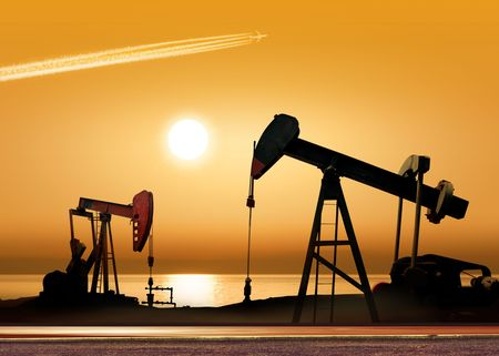 Working oil pump in rural place at sunset  Stock Photo