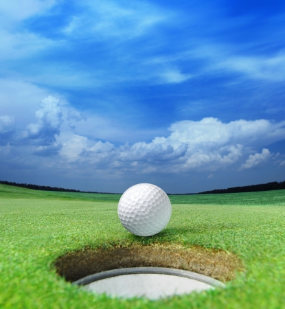 golf ball on lip of cup of lovely beautiful golf course photo