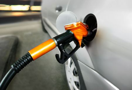 petrol pump: grey car at gas station being filled with fuel Stock Photo