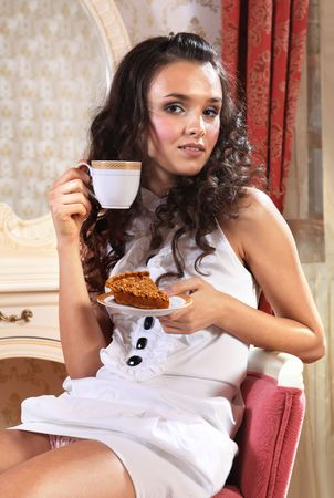 footsie: girl with piece of cake and cup of tea with comehither eyes
