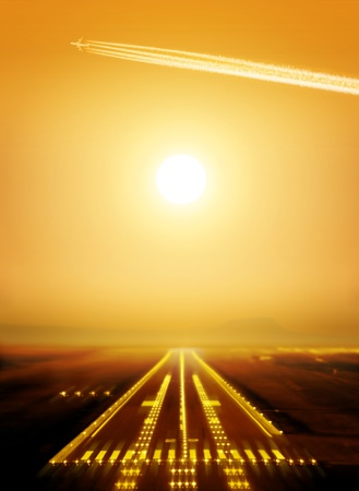airport runway: passenger plane fly up over runway from airport at sunset Stock Photo