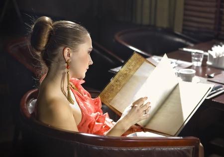 beautiful woman looks on menu at expensive restaurant