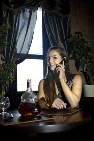 woman sits at the table and speaks by mobile phone in vintage restaurant photo