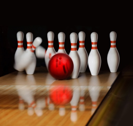 bowling strike: orange ball does strike on tenpin bowling in skittle-ground