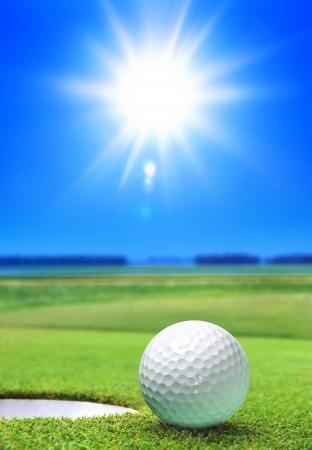 golf ball op groene koers in de buurt van de bunker Stockfoto