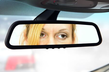 woman sits on drivers seat and Looks in the rear-view mirror photo