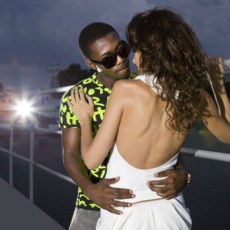 amorousness: couple of lovers in harbour at night, afro-american man embraces caucasian woman Stock Photo