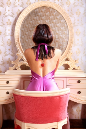woman mirror: beautiful young lady at mirror admires reflexion in the bedroom Stock Photo