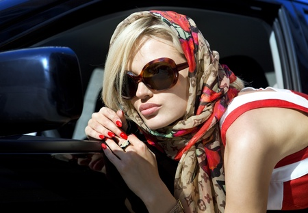 modern fashion blonde woman in dark sunglasses in the city photo