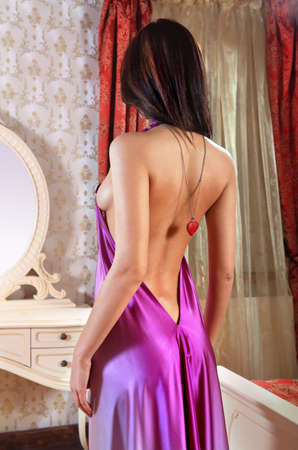 beautiful young lady at mirror fits on new dress in the bedroom photo