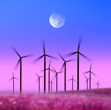 silhouette of wind turbines generating electricity on night sky photo