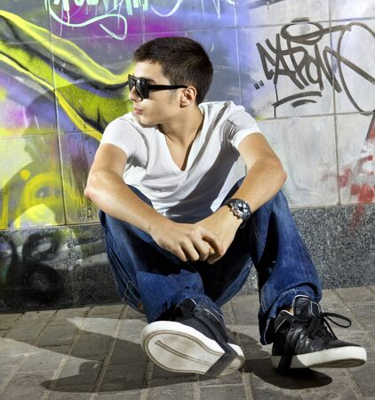 young man sitting in front of a colorful graffiti wall