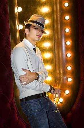 young man with glass of champagne near the mirror in cabaret photo