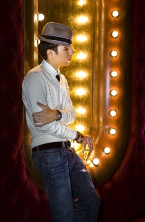 gigolo: young man with glass of wine near the mirror in cabaret Stock Photo