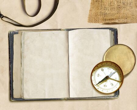 ancient logbook and compass on faded paper, copyspace photo