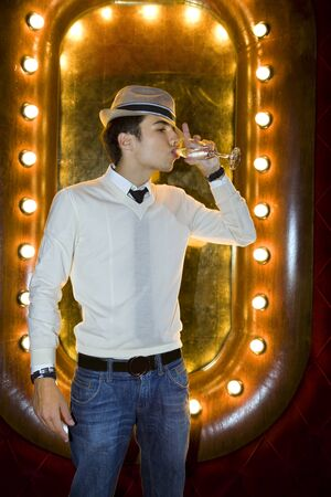 Man with hat in night club, with a glass of wine on the hand  photo