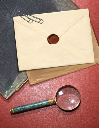 handglass: dorsal view of military top secret envelope with magnifier Stock Photo