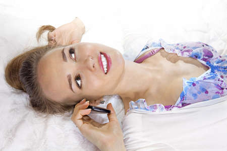 Pretty woman lying on the bed holding her smartphone Stock Photo - 9396410