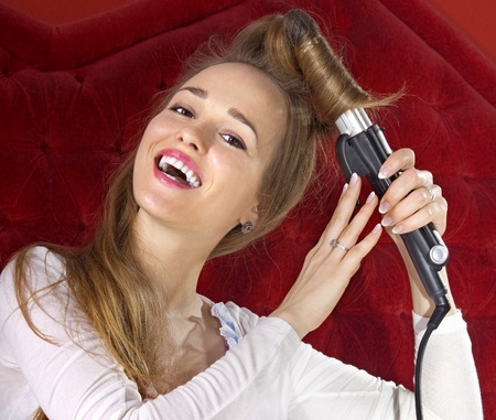 happy beautiful young girl curling her hair photo