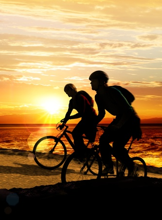 Couple on bicycles on the brink of a rock near sea