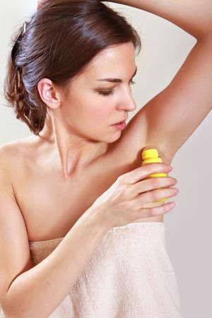 axilla: beautiful woman applying roll-on antiperspirant