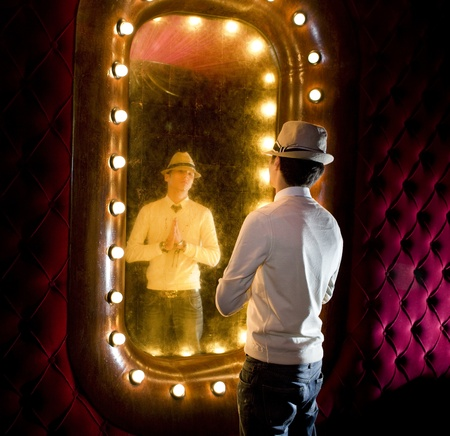 retro young man looks at itself in mirror photo