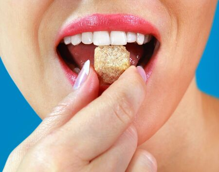 part of beautiful girl eats piece of sweets photo
