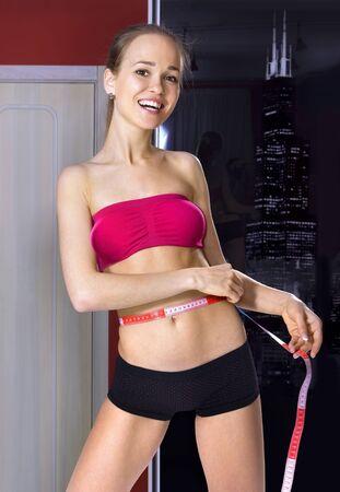 cintura perfecta: Mujer joven feliz medidas de su cuerpo en su casa Foto de archivo