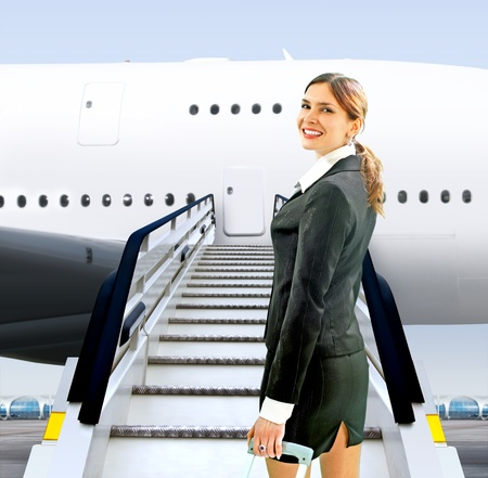 beautiful flight attendant near moving ramp in airport photo