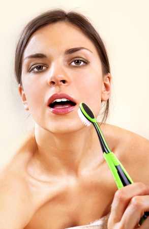 beautiful woman with tooth-brush cleans her teeth photo