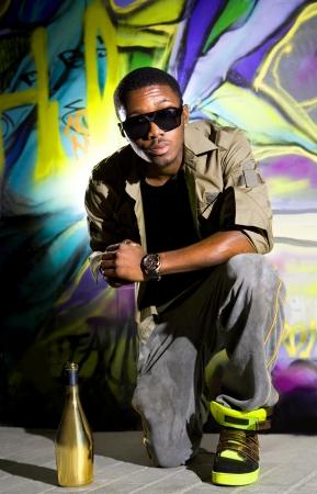 rapper: los j�venes afro-americanos hombre que estaba sentado en frente de colorido pared de graffiti Foto de archivo
