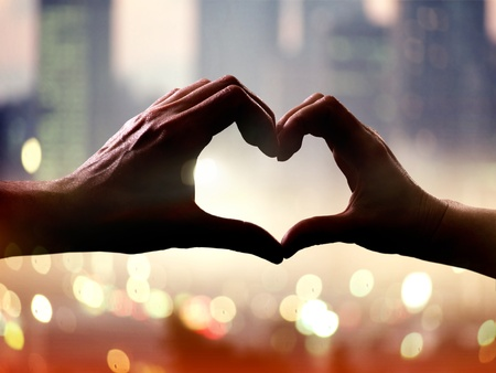 Silhouette of hands in form of heart when sweethearts have touched Stock Photo