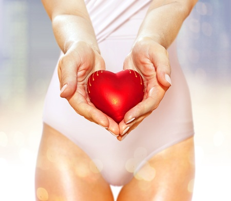 lovemaking: artificial red heart on hands of beautiful woman