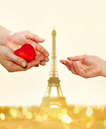 artificial red heart on hands of man for woman on Eiffel Tower background photo
