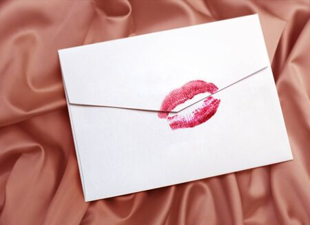 wooing: white envelope with lipstick kiss on  gentle silk