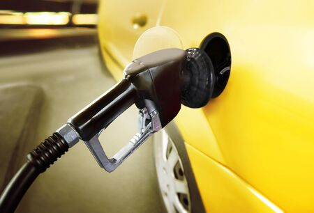 fillup: yellow car at gas station being filled with fuel Stock Photo