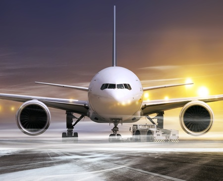 white plane in airport at non-flying weather, blowing snow