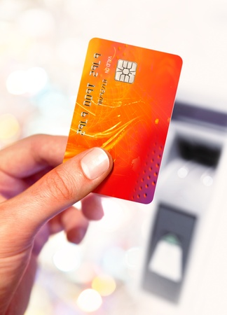 Close-up of man hand holding plastik credit card near ATM
