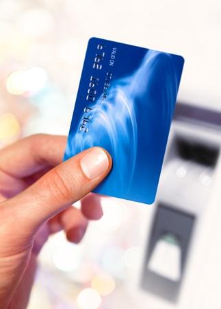 automatic transaction machine: Close-up de la mano del hombre que sostiene la tarjeta de crédito cerca de plastico ATM