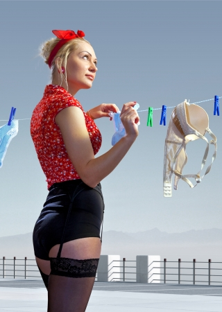 hangs: beautiful housewife hangs out washed underwear for drying Stock Photo