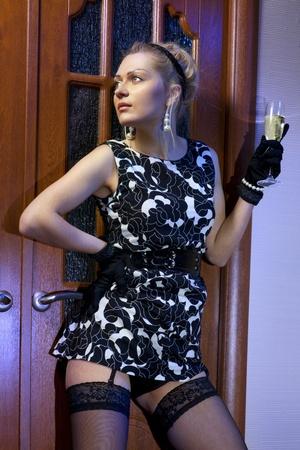 donna ricca: bella donna ricca in abito nero con un bicchiere di champagne