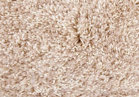 beige carpet texture, frontal view close-up woolen fibers photo