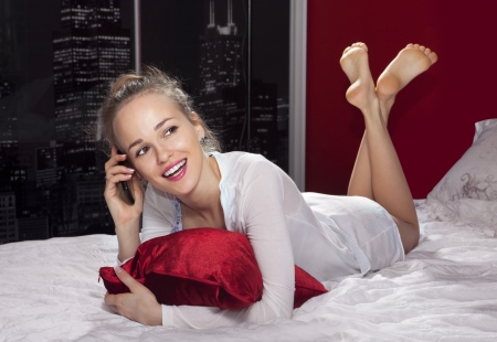 Pretty woman lying on the bed holding her smartphone photo