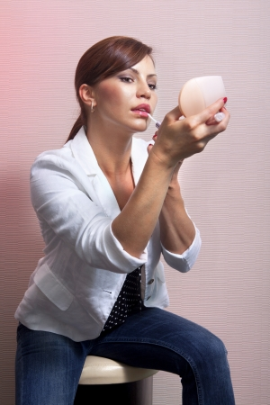 Pretty woman applying her make-up looking at mirror Stock Photo - 13603897