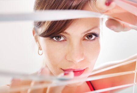 Beautiful woman are looking through jalousie  Stock Photo