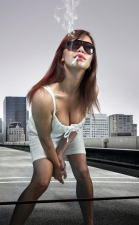 vulgar: Beautiful woman on urban background smoking cigarette