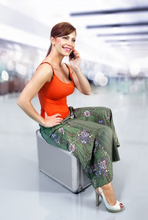 airport lounge: young beautiful girl speaks by mobile phone at airport