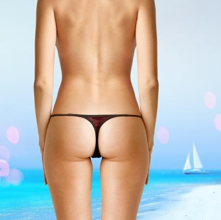 tanning: back of woman in bikini on beach Stock Photo