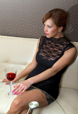 beautiful happy woman in black dress on sofa with glass of champagne Stock Photo