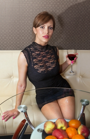 luxury hotel room: beautiful happy woman in black dress on sofa with glass of wine